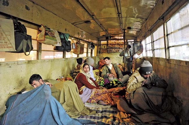 Buses are becoming makeshift 'night shelters' for homeless patients in Delhi. Each bus can accomodate 28 people at a time. Pic/AFP