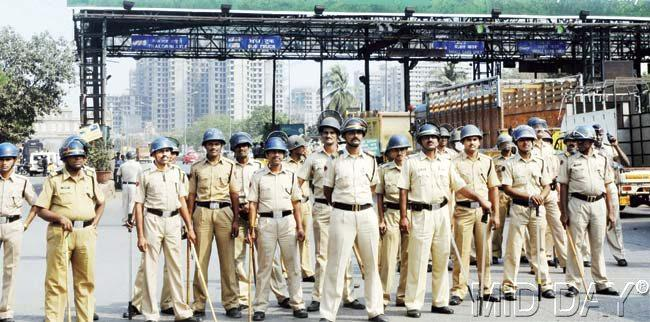 Police platoon stand guard outside Dahisar toll plaza to prevent MNS workers from vandalising it. Pics/Nimesh Dave