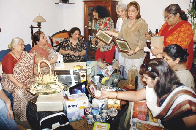 Heena Udeshi (l) with others collating  items for an earlier garage sale