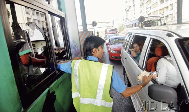 An attendant operates from a broken booth window at Mulund toll Plaza yesterday. Pic/Sameer Markande